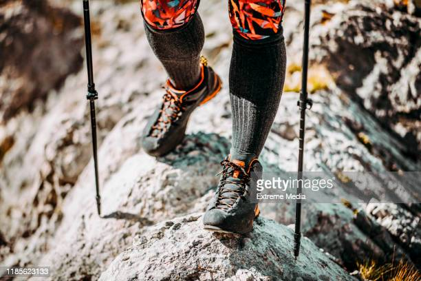 lower portion of a hiker going over treacherous terrain in hiking boots, and using walking sticks - low section stock pictures, royalty-free photos & images