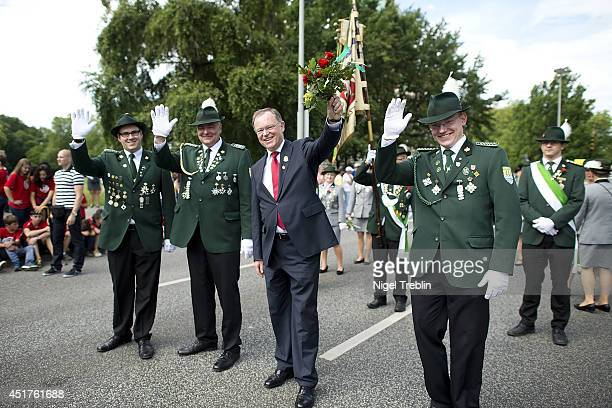 Lower Saxony Governor Stephan Weil waves to the crowd during a parade at the world's largest shooting fair, known as Schutzenfest, on July 6, 2014 in...