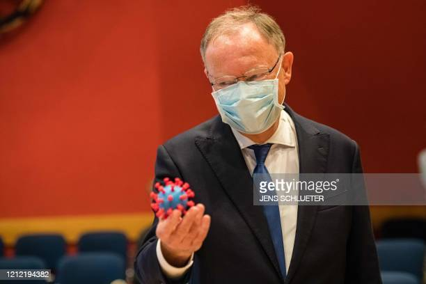 Lower Saxony's State Premier Stephan Weil holds a model of the novel coronavirus SARS-CoV-2 in his hand as he visits the Helmholtz Center for...