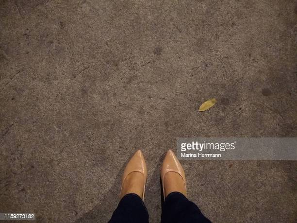 lower section of female leg on gray sidewalk - nette schoen stockfoto's en -beelden