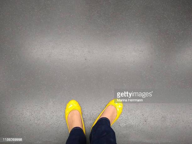 lower section of female legs on gray floor - gray shoe stock pictures, royalty-free photos & images