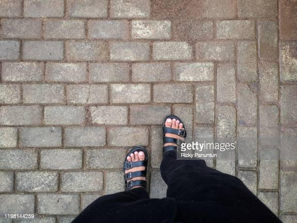 lower section of male legs on paving floor - sezione inferiore foto e immagini stock