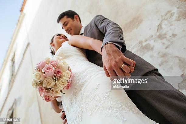 Lower shot of a Hispanic newlywed couple holding hands