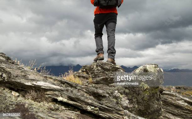 lower torso of hiker on summit ridge - black trousers stock pictures, royalty-free photos & images