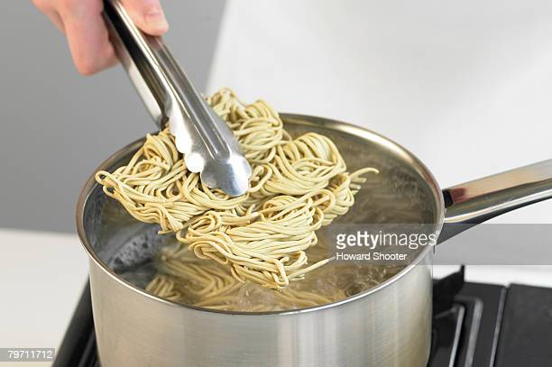 Lowering noodles in to a pan, close up