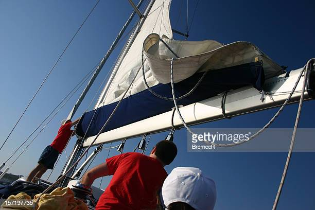 lowering the sail - catamaran sailing stock photos and pictures