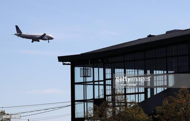 A lowflying aircraft heading towards Logan Airport for a landing passes by a glass enclosure at the shuttered Suffolk Downs horse racing track in...