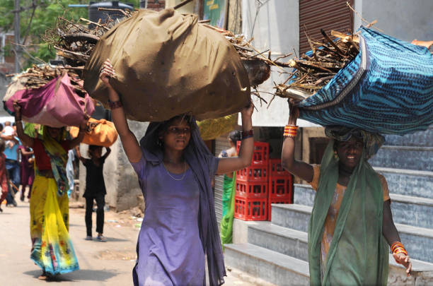 Lowincome Indian women carry home branches and twigs to use as fire wood when cooking in Amritsar on July 18 2009 Cooking without adequate...