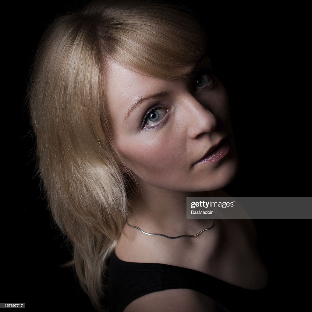 Lowkey portrait of a beautiful young girl looking into camera : Stock Photo