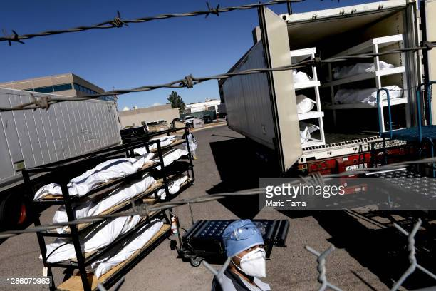 Low-level inmate from El Paso County detention facility prepare to load bodies wrapped in plastic into a refrigerated temporary morgue trailer in a...