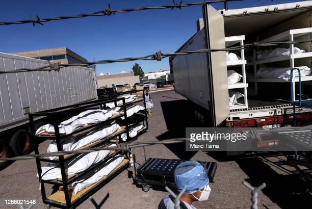 Low-level inmate from El Paso County detention facility waits to help load bodies wrapped in plastic into a refrigerated temporary morgue trailer in...