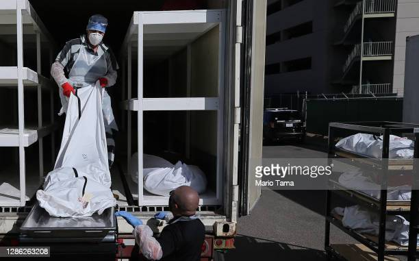 Low-level inmate from El Paso County detention facility works loading bodies wrapped in plastic into a refrigerated temporary morgue trailer in a...