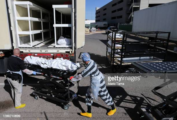 Low-level inmate from El Paso County detention facility works while loading bodies wrapped in plastic into a refrigerated temporary morgue trailer in...