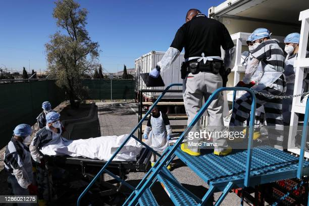 Low-level inmates from El Paso County detention facility load bodies wrapped in plastic into a refrigerated temporary morgue trailer in a parking lot...