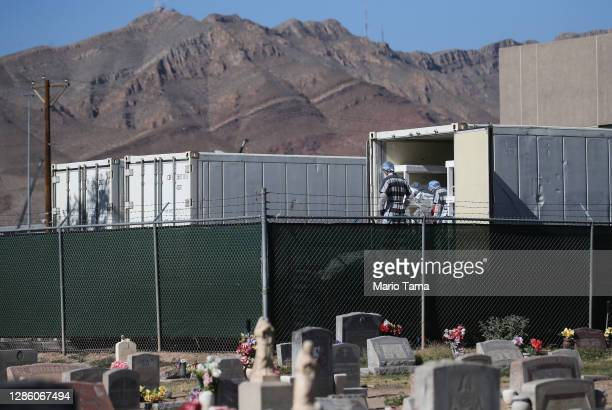 Low-level inmates from El Paso County detention facility prepare to load bodies wrapped in plastic into a refrigerated temporary morgue trailer in a...
