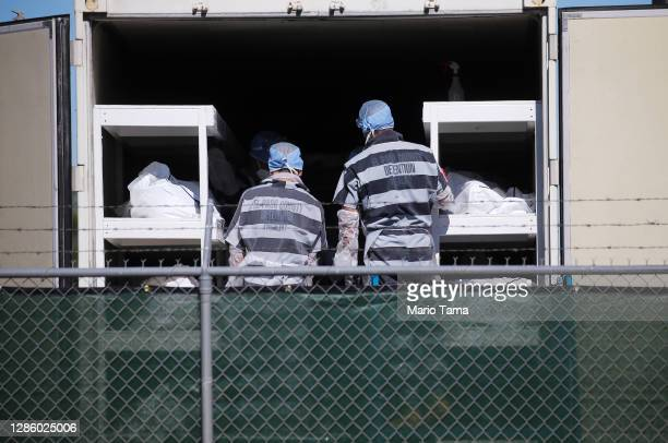 Low-level inmates from El Paso County detention facility work loading bodies wrapped in plastic into a refrigerated temporary morgue trailer in a...