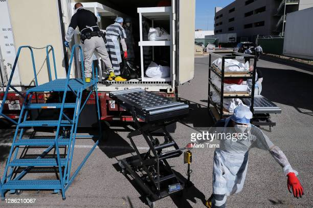 Low-level inmates from El Paso County detention facility work while loading bodies wrapped in plastic into a refrigerated temporary morgue trailer in...