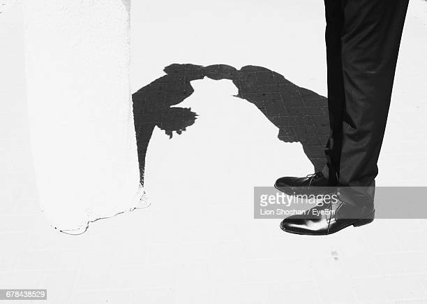 Lows Section Of Bride And Bridegroom Standing On Footpath With Shadow