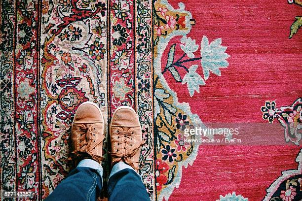 low-section of man standing on old fashioned rug - persian rug stock photos and pictures