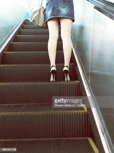 low-section of woman standing on escalator - ankle length stock pictures, royalty-free photos & images