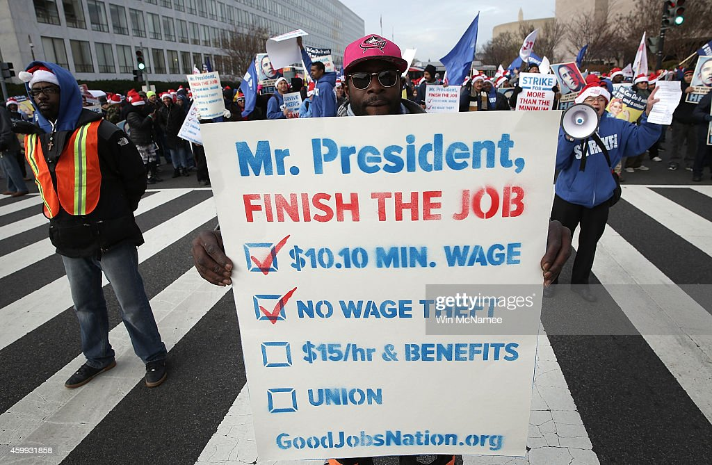 Low-wage federal contract workers block rush hour traffic on Independence Avenue while demanding presidential action to win an increase to $15 an hour wage December 4, 2014 in Washington, DC. A number of workers were expected to walk off their jobs later in the day as part of the protest.