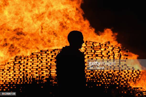 Loyalist are silhouetted as they gather in front of the bonfire on the Sandy Row area on July 12 2017 in Belfast Northern Ireland The lighting of the...