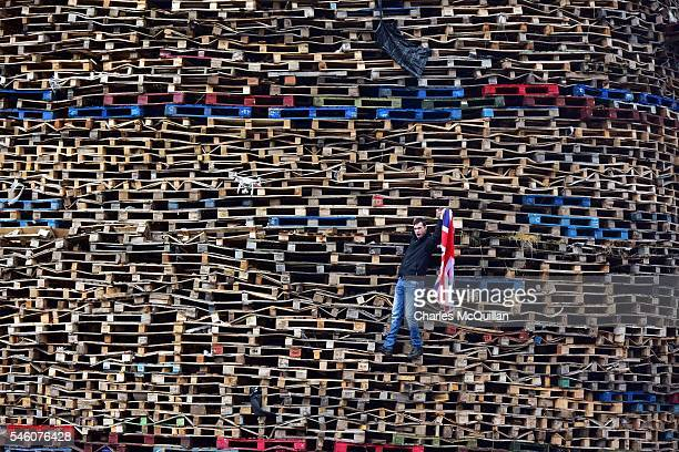 Loyalist poses for a drone as he is filmed making final preparations to a huge bonfire on the Ballymacash estate on July 11 2016 in Belfast Northern...