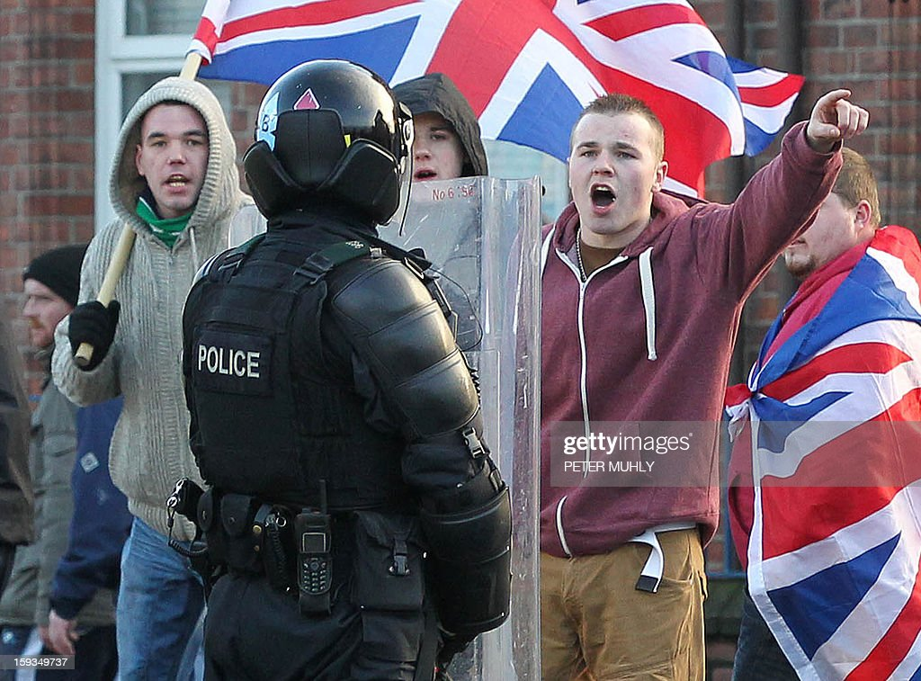 Loyalist protesters waving Union Flags shout at police in riot gear during clashes between, loyalists, nationalists and the police in east Belfast, Northern Ireland on January 12, 2013 after the latest loyalist march against the decision to limit the days on which the Union Flag would be flown over Belfast City Hall. Northern Irish demonstrators loyal to Britain clashed with nationalists and police on Saturday in fresh protests against curbs on flying the British flag, leaving four officers injured, police said. The clashes were the latest to blight the British province after more than five weeks of violent disorder over the flag issue.