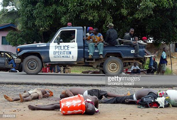 A loyalist vehicle passes the bodies of several governmental combatants executed summarily by their officers after being accused of pillaging and...