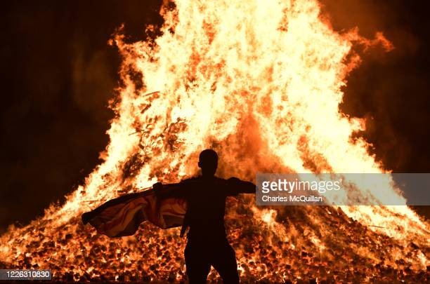 A loyalist waves a union jack flag at the Ballycraigy estate 11th night bonfire on July 11 2020 in Antrim Northern Ireland Loyalists traditionally...