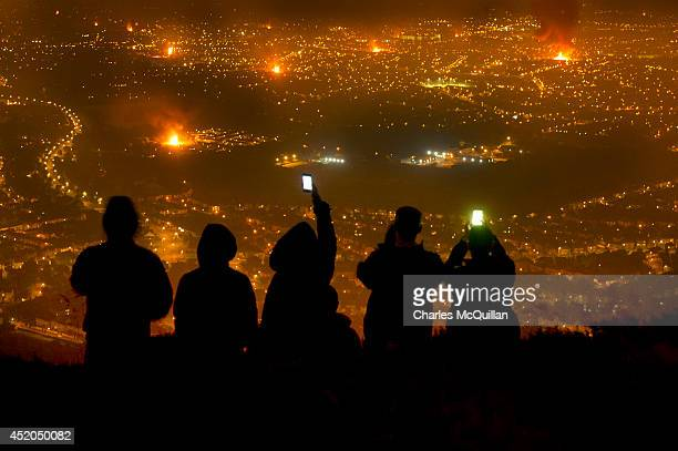 Loyalist youths stand and take photographs with their mobile phones of bonfires burning across Belfast from the Cave Hill mountain high above the...