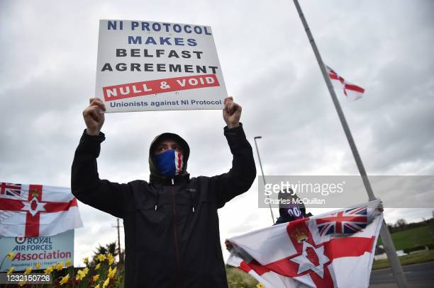 Loyalists hold up placards during an anti Northern Ireland Protocol protest against the so called Irish Sea border on April 6, 2021 in Larne,...