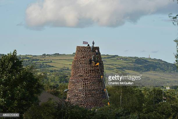 Loyalists stack pallets and tyres on top of their bonfire construct in preparation for their 11th night bonfire at the New Mossley estate on July 9...