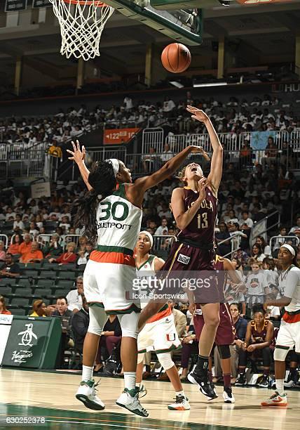 Loyola guard/forward Katie Salmon shoots against Miami forward/center Erykah Davenport during an NCAA basketball game between Loyola Chicago...