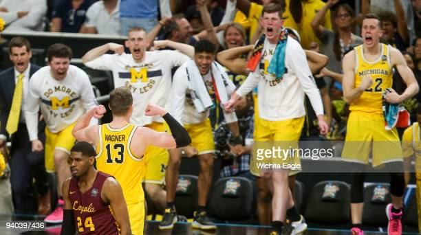 Loyola's Aundre Jackson turns away as Michigan's Moritz Wagner turns and flexes at the bench following a 3pointer late in the second half during an...