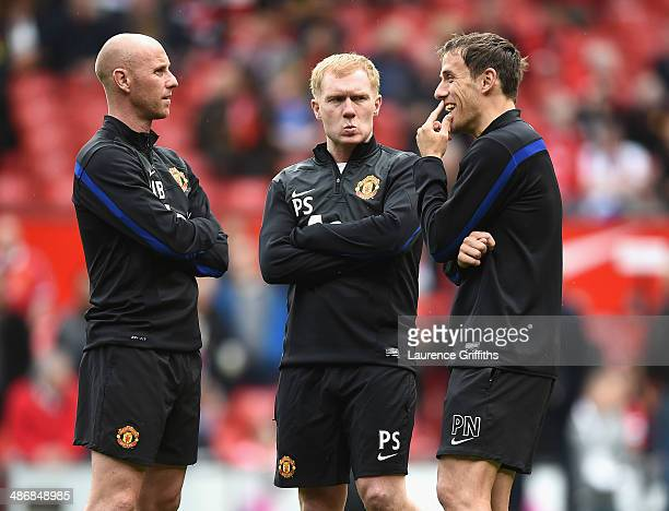 lr Nicky Butt Paul Scholes and Phil Neville of Manchester United watch over the players during warm up during the Barclays Premier League match...