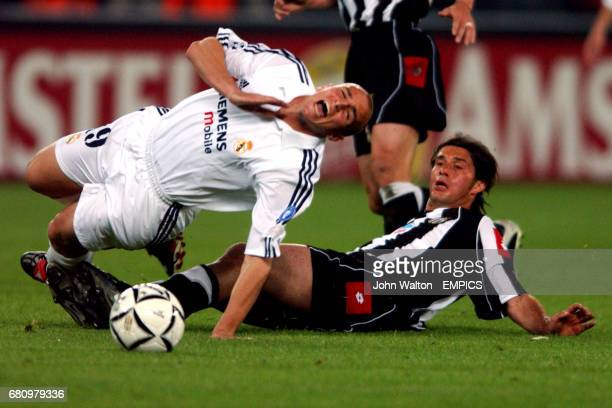 lr Real Madrid's Esteban Cambiasso is sent flying under the challenge of Juventus' Alessio Tacchinardi