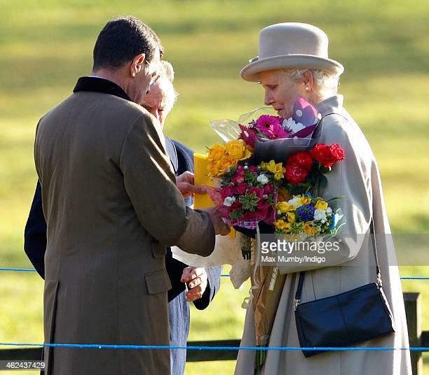Lt Col Charles Richards and Sir Jackie Stewart help Mary Morrison carry flowers which members of the public had brought to give to Queen Elizabeth II...