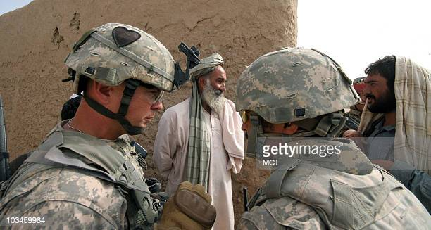 Lt Col David Flynn left commander of the 101st Airborne Division's 'Top Gun' field artillery battalion stationed in southern Afghanistan listens to a...