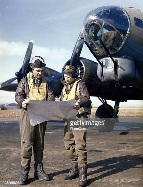 Lt Col Louis G Thorup and 1st Lt John A Webb officers of the United States' 8th Air Force stand before their B17 Flying Fortress holding an unfurled...