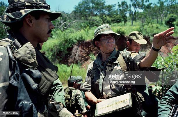 Lt Colonel Domingo Monterrosa right speaks with one of his company commanders left from El Salvador's Atlacatl Rapid Reaction Battalion as soldiers...