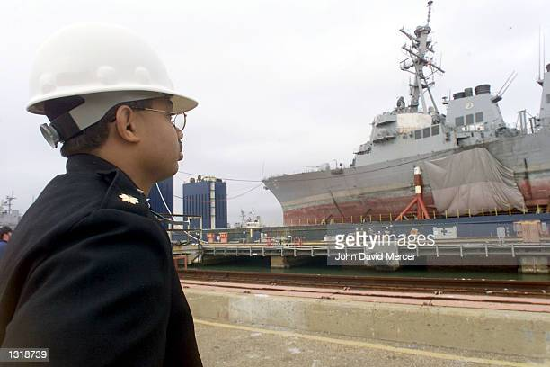 Lt Commander Charles Owens of the US Navy watches as the USS Cole is returned back to the United States December 13 2000 at Ingalls Shipbuilding in...