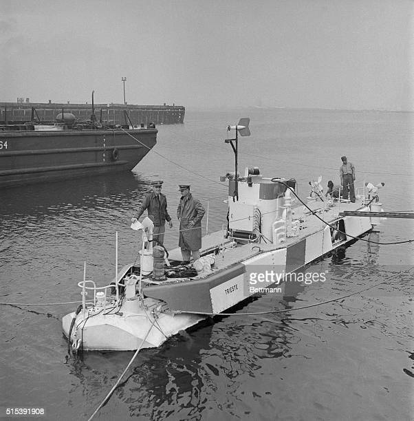 Lt Donald Keach and Lt George Martin who will man the Navy's deepdiving bathysphere Trieste stand on bow as sailors aft make craft ready for sea The...
