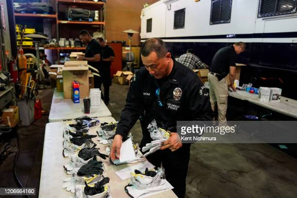 Lt Jay Hom helps assemble kits consisting of an N95 mask work gloves and nitrile gloves as he and other LAPD personnel assemble personal safety kits...