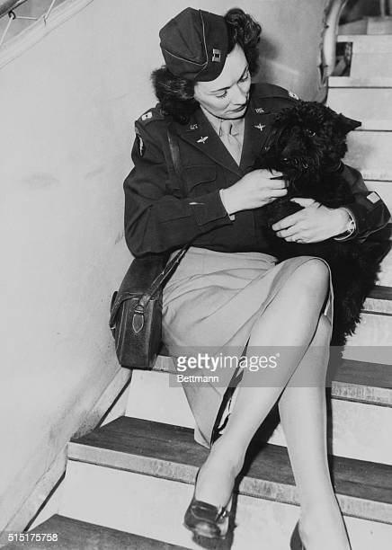 Lt Kay Summersby sits on a flight of stairs holding a Scottish terrier
