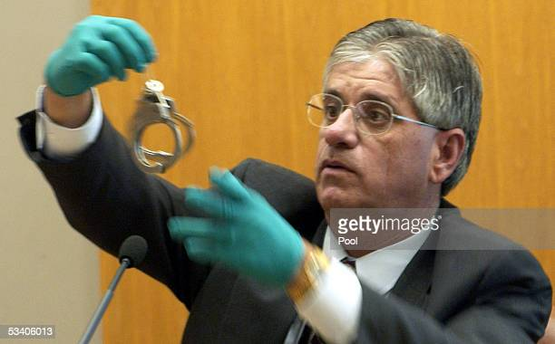 Lt Ken Landwehr holds up a pair of handcuffs which were used in one of the crimes during Dennis L Rader's sentencing hearing August 18 2005 in...