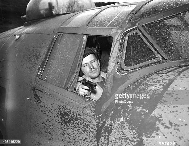 Lt Nels Lofgren copilot of a B24 seated in the cockpit of his plane with a 45 automatic in the same position in which he fired at Japanese Zero...