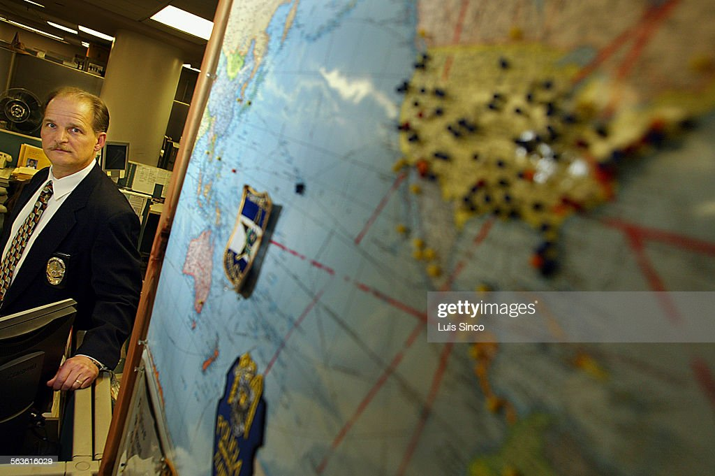 Lt  Raymond Foster stands beside a map that shows distant points