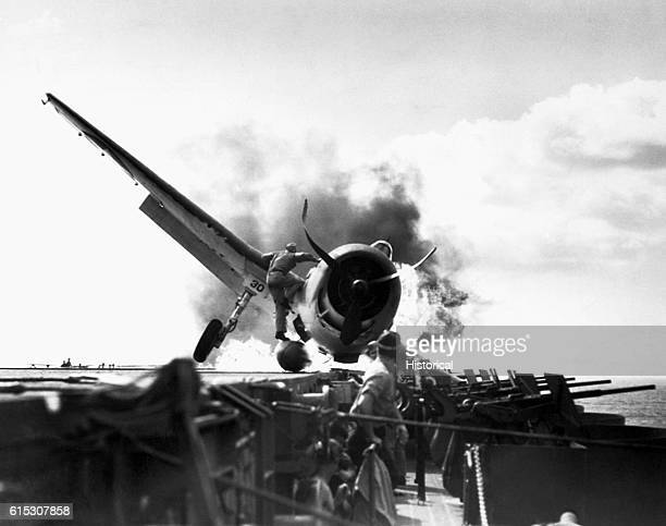 Lt Walter Chewning catapult officer aboard the USS Enterprise clambers up the side of a downed F6F Hellcat to assist the pilot Ensign Byron Johnson...