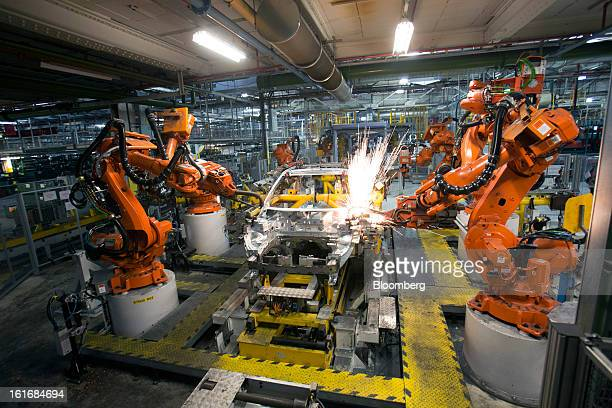 ABB Ltd robotic arms weld the aluminum panels of an SUV automobile body shell as it travels along the production line at Jaguar Land Rover Plc's...